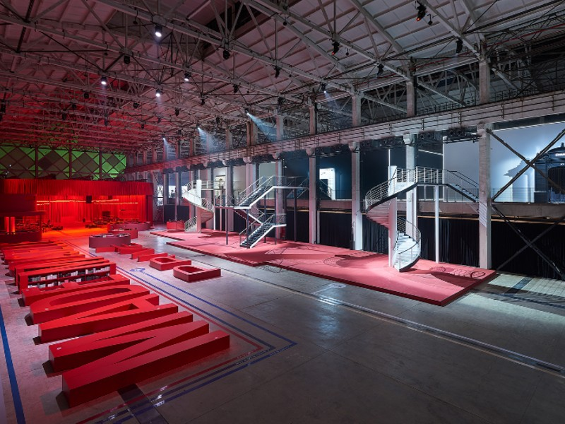 "The red benches spell ""Mademoiselle Privé"". At the far left corner is a space dedicated to the Métier d'Art (or traditional crafts) arm of Chanel. In the middle are spiral stairs leading exhibition-goers to the second floor. Image courtesy of Chanel"