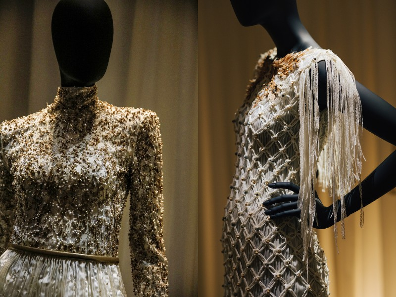 On the right, a blouse intricately embellished with diamantes and pearls paired with a pleated skirt. On the right, a lace-knitted net dress worn over a pleated dress. Image courtesy of Chanel