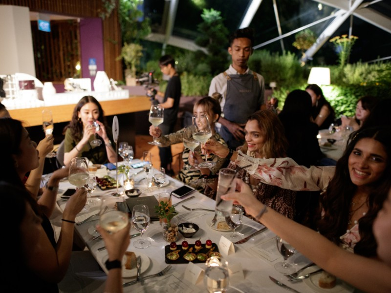On the right, Vietnamese fashion Instagrammer, Salim Hoang Kim Ngan, Indian influencers, Monalisha Mahapatra and Mitali leans in for a toast at Pollen. Image courtesy of Charles & Keith.