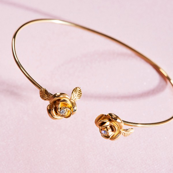 An open-hoop bangle punctuated with roses in 18-carat gold and diamonds, available at S$4,550.