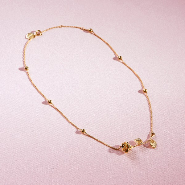 A chain necklace punctuated with spheres and a rose pendant in 18-carat gold, available at S$3,640.