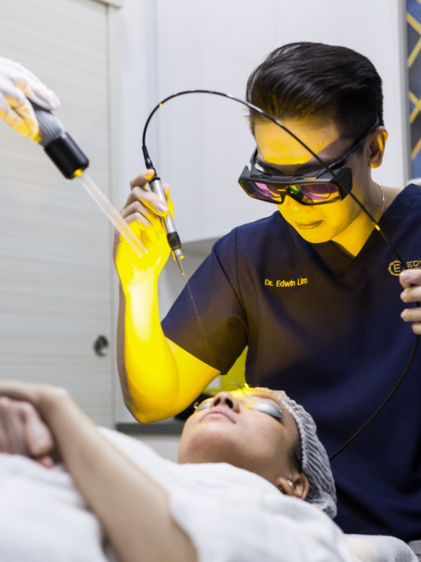 In Dr. Edwin Lim's hands is the laser jet. Positioned before him is a tube emitting a steady stream of cool air to combat the searing heat from the laser. Image courtesy of Dr. Edwin Lim Medical Aesthetic Clinic